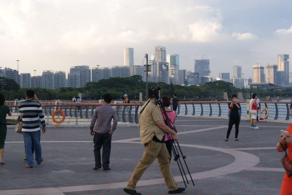 Парень-иностранец фотографирует залив Шэньчжэнь, и городские виды Шэньчжэня и Гонконга