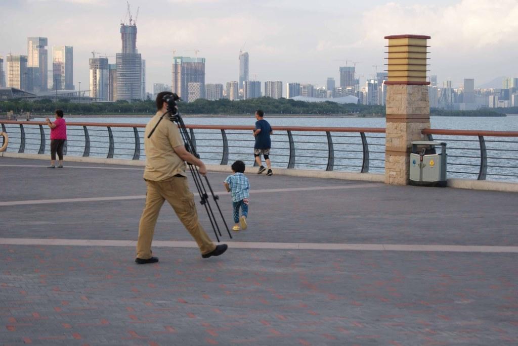 Парень-фотограф готовится к съёмке с бетонной конструкции в заливе Шэньчжэнь